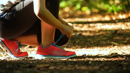 cipőfűző : Female runner lacing her sneakers on a forest trail