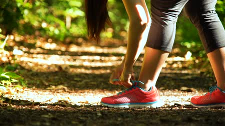 cipőfűző : Female runner lacing her sneakers on a forest trail in 60fps