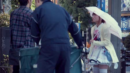 TOKYO, JAPAN - JUNE, 24 2015: Woman solicits customers to a maid cafe in Akihabara. Stok Video