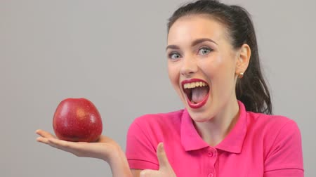 póló : Happy beautiful girl holding red apple, thumbs up Stock mozgókép
