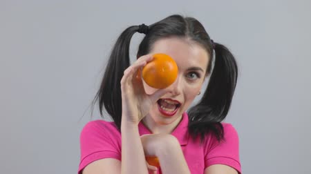 ajkak : Attractive girl holds up a oranges and laughs Stock mozgókép