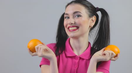 póló : Young female knocks on oranges and laughs Stock mozgókép