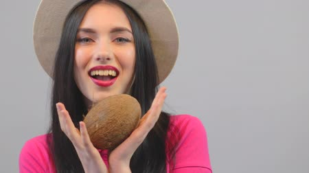 póló : Young woman shows a coconut. Pink polo and hat on a white background