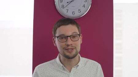 hodnocení : Man with glasses says something, he stands on the background with a clock. The office has a window with light outside Dostupné videozáznamy