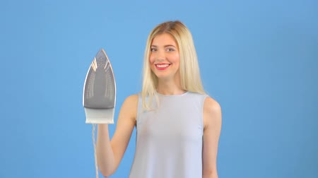 ferro : Attractive young woman ironing and smiling to the camera