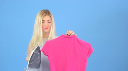 housekeeper : Young woman ironing pink t-shirt and smiling to the camera