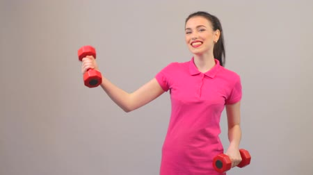 póló : Young adult woman training biceps with dumbbells, sports clothing, fitness Stock mozgókép