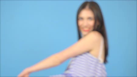 ожерелье : De-focused, young beautiful brunette in a blue dress dancing