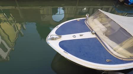 Close-up motor boat, canal in Venice, Italy. Reflection in water
