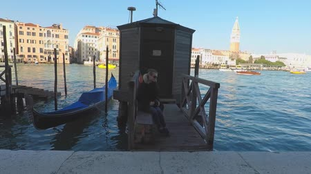 Girl sits near the canal and gondola in Venice, Italy