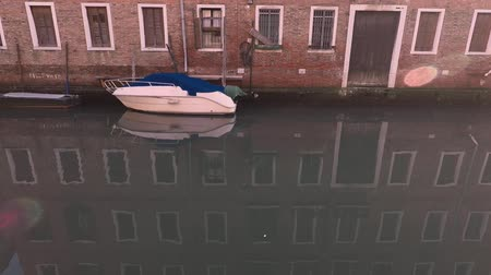 White motor boat, canal in Venice, Italy. Reflection in water