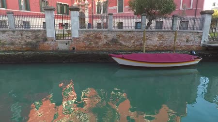 Moored motor boat, canal in Venice, Italy. Reflection in water