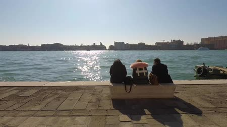 People are sitting on the bench watching the sea in Venice, Italy Dostupné videozáznamy