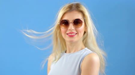 arcszín : Beautiful blond girl with long straight hairs, wind blowing sensual portrait Stock mozgókép