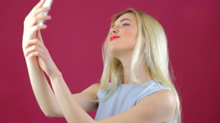 facetime : Blonde girl takes selfies of herself with smartphone Stock Footage