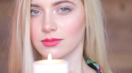 Ко : Sad attractive young women with candle in arms. Never again. Feel pain, lost someone