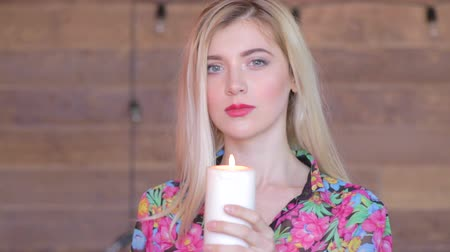 Ко : Attractive young women with candle in arms. Never again. Feel pain, lost someone