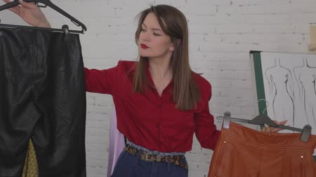 Shopping leather clothes, young woman chooses skirt and trousers Dostupné videozáznamy