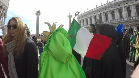 Carnival of Venice, Italy – February 2018. Costumed actors with italian flag walk at St Marks square. Actor with green cloak, many tourists around Dostupné videozáznamy