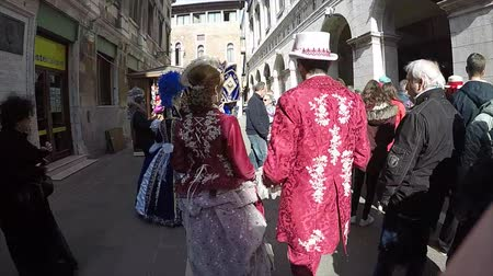 Carnival of Venice, Italy – February 2018. Costumed actors cross walk through narrow streets to the St Marks square to find photographers and media