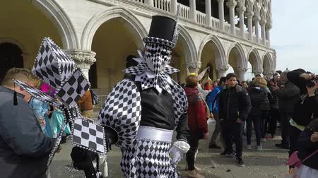 Carnival of Venice, Italy – February 2018. Costumed actor walk through St Marks square. Actor with black and white mask pose, random tourists. Carnevale di Venezia