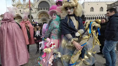 Carnival of Venice, Italy – February 2018. Costumed actor walk through St Marks square. Actors in masks pose, random tourists around. Carnevale di Venezia