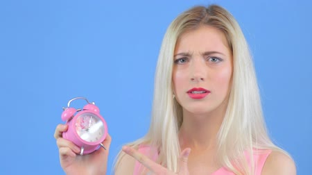 утешитель : Attractive young woman holds an alarm clock