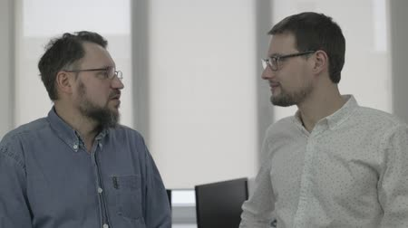 Scene of two men talking in office