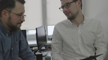 Close up of two men in glasses talking in office Dostupné videozáznamy