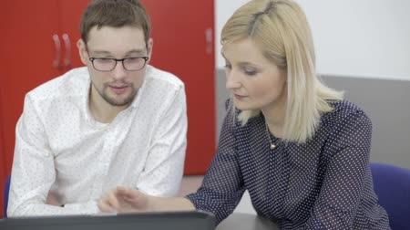 Man in glasses and young blonde woman with laptop in the office Vídeos