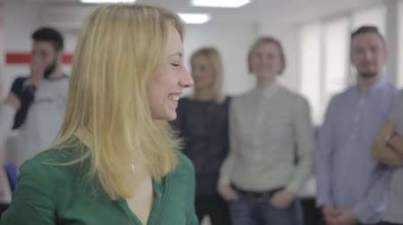Young caucasian attractive woman smiling against people talk, office scene