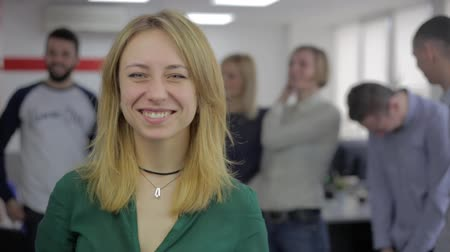 Caucasian attractive woman smiling against people talk, office scene