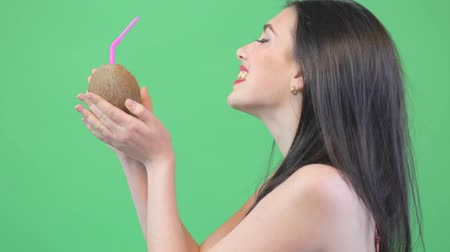 Beautiful woman with coconut posing in bikini over green screen. Hat in hand, summer style, have fun, attractive brunette woman Dostupné videozáznamy