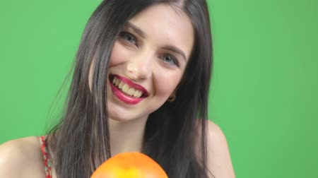 Beauty model girl takes orange. Beautiful joyful young woman against chroma key background Vídeos