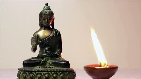 aromaterapia : Statuette of Buddha and a burning candle.
