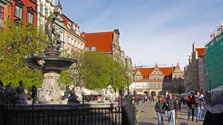 europe population : GDANSK, POLAND - May 07 2017: Neptune statue and fountain in the old town of Gdansk. Tourists walking along the old town of Gdansk.