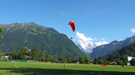 ledovec : INTERLAKEN, SWITZERLAND: Paragliders in front of the Alps in Interlaken, Switzerland. Interlaken is a resort town in the Interlaken-Oberhasli administrative district in the Swiss canton of Bern. Dostupné videozáznamy
