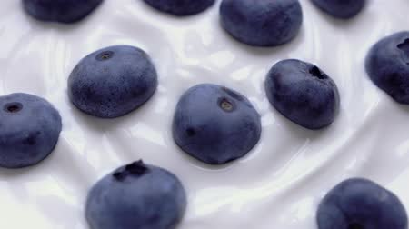 kék háttér : Closeup Blueberries in natural yogurt rotating. Seamless looping, 4k. Fruit background.