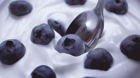jagody : Eating blueberries with cream by spoon, fruit background. 4k. Wideo