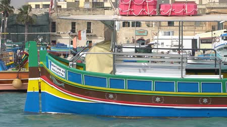 укрепленный : Marsachlokk - MALTA, April, 2018: Colorful Maltese boats in the harbor in Malta in the fishing village of Marsachlokk. Стоковые видеозаписи