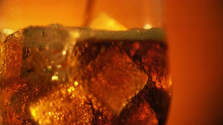 refraksiyon : Cola pouring into the glass with Ice cubes and bubbles. Food background. Soda Close-up. Stok Video