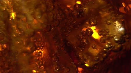 Cola in the glass with Ice cubes and bubbles rotating. Food background. Soda Close-up.