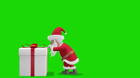 святой : Santa Claus Pushing Gift. Merry Christmas and Happy New Year 2020 animation. Santa Claus with a Christmas gift near the Christmas tree. With alpha channel.