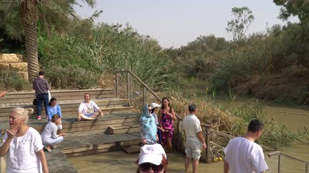 holy heaven : Jordan River, Israel - November 2019: Yardenit Baptismal Site. Christian pilgrims during mass baptism ceremony at Jordan River in North Israel.