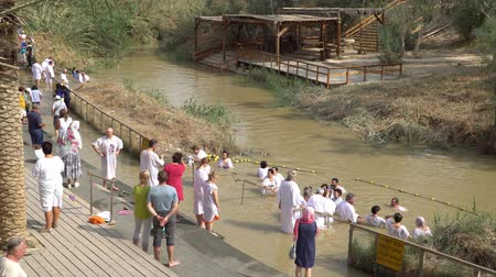 divino : Jordan River, Israel - November 2019: Yardenit Baptismal Site. Christian pilgrims during mass baptism ceremony at Jordan River in North Israel.