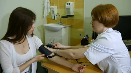 complaints : The doctor measures the pressure of the girl Stock Footage