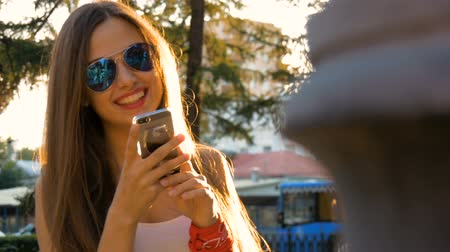 Attractive girl using mobile phone in a city.
