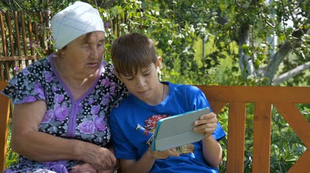 grandchild : Grandson showing grandmother how to use tablet Stock Footage