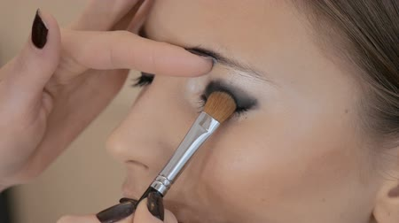 применения : Professional makeup artist applies makeup to a beautiful model. Colors eye