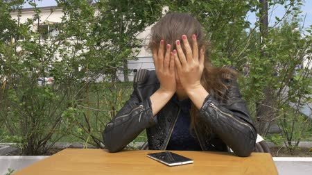 kötü : Sad beautiful girl sitting at a table in a cafe. Reads sms on a smartphone. Has hugs his head with his hands Sadness and longing, hopelessness.